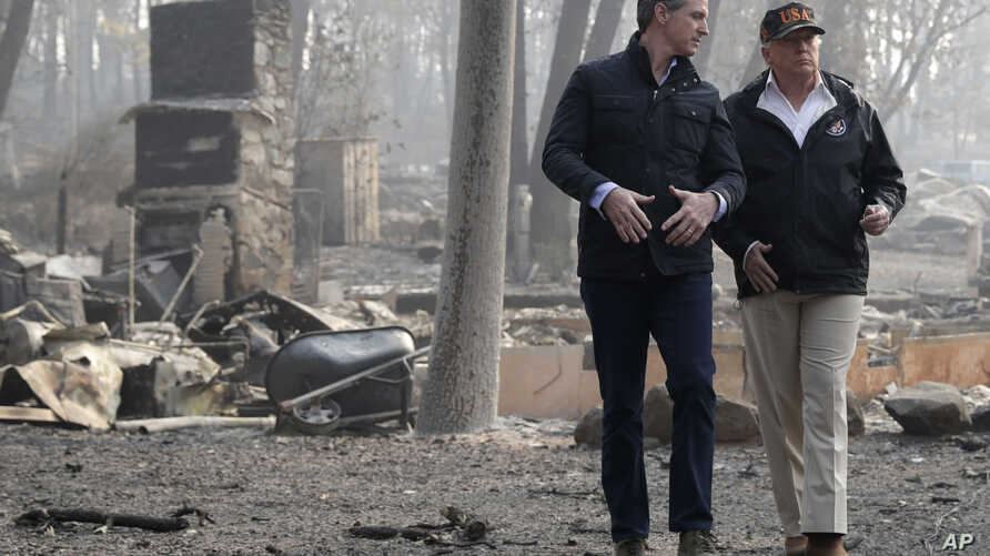 President Donald Trump talks with California Gov. Gavin Newsom during a visit to a neighborhood destroyed by the wildfires, Nov. 17, 2018, in Paradise, Calif.