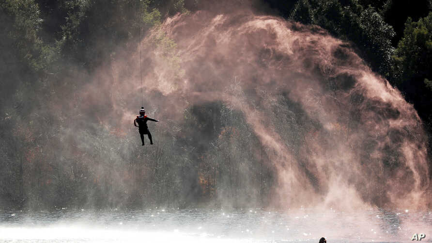 A soldier is lowered from a helicopter to practice rescuing a person in the water during a joint rescue operation in the U.S.-China Disaster Management Exchange (DME) in Kunming, China's Yunnan Province, Friday, Nov. 18, 2016.