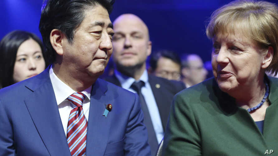 German Chancellor Angela Merkel, right sits with the Prime Minister of Japan Shinzo Abe, at the opening of the CeBIT trade fair in Hanover, Germany, March 19, 2017.