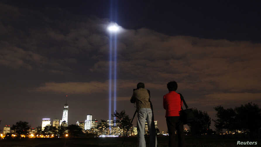 The annual Tribute in Light is tested in New York's Lower Manhattan as a man takes a picture at Liberty State Park in Jersey City, New Jersey, September 9, 2013.