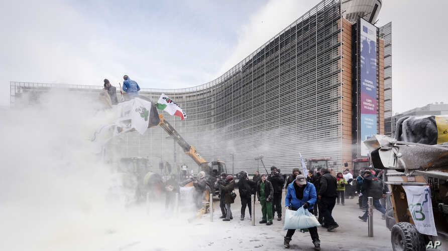 European dairy farmers spray the EU Council building with milk powder to protest the crisis in their sector, in Brussels, Jan. 23, 2017.