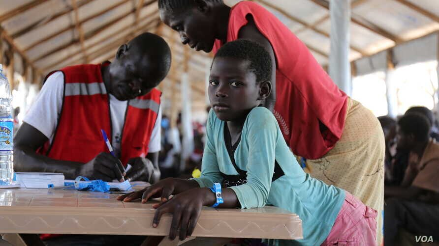 South Sudanese girl waits for her mother to finalize their paperwork in the Imvepi refugee settlement's processing center. Photo taken on March 31 in Arua, Uganda.