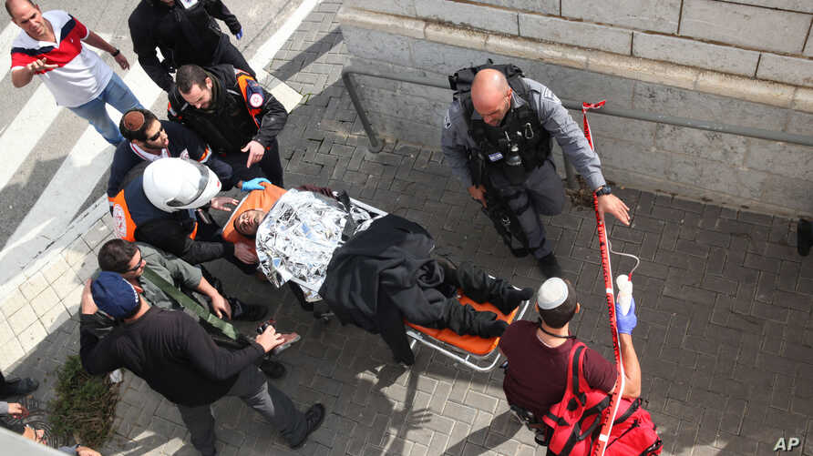 Israeli medics carry a wounded Israeli following a stabbing attack in a light rail train in Jerusalem, Nov. 10, 2015.