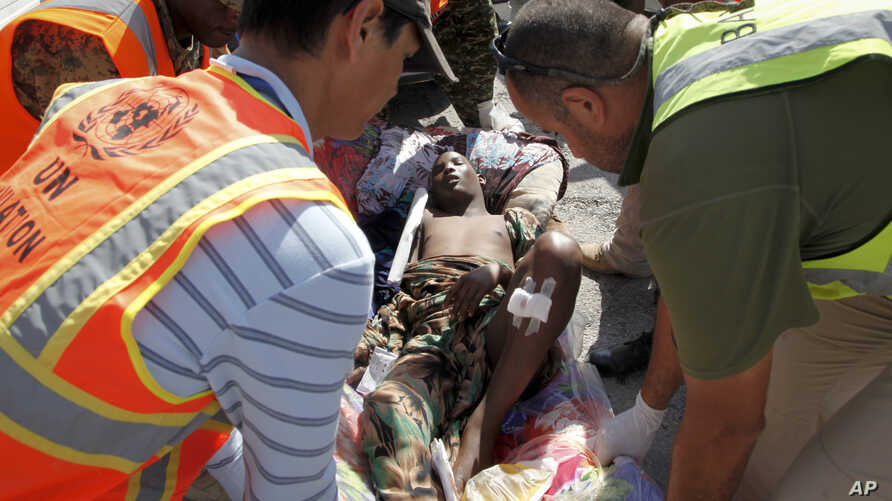 United Nations and other workers assist a young wounded man after he and others were airlifted to Mogadishu for treatment, following Sunday's attack on restaurants in the city of Baidoa, at the airport in Mogadishu, Somalia, Feb. 29, 2016.
