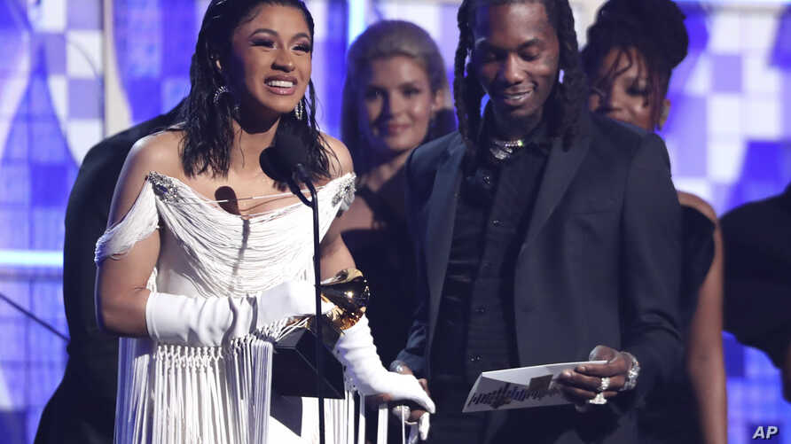 """Cardi B, left, accepts the award for best rap album for """"Invasion of Privacy"""" as Offset looks on at the 61st annual Grammy Awards on Sunday, Feb. 10, 2019, in Los Angeles."""