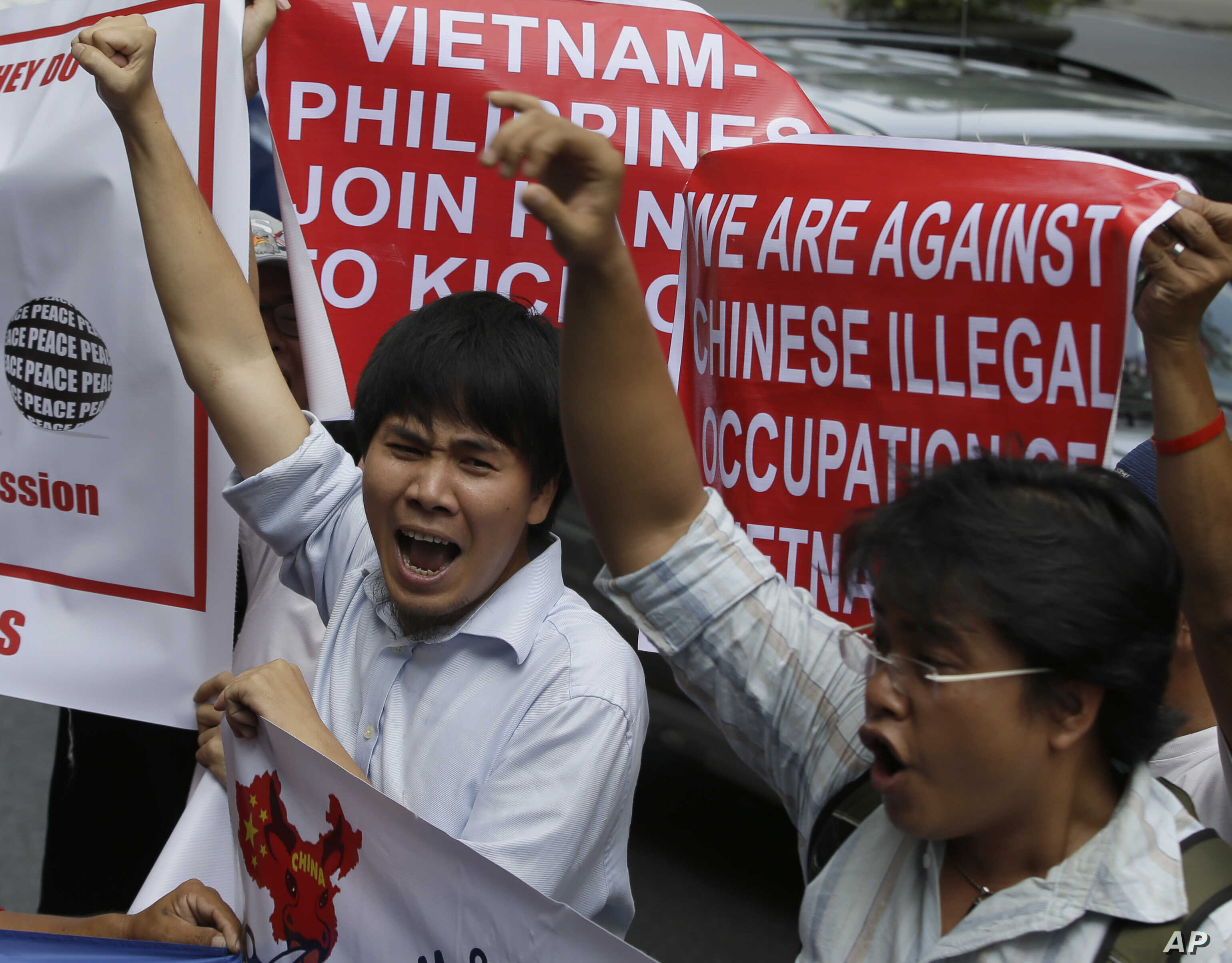 Vietnamese expatriates shout slogans in front of the Chinese Consulate at the financial district of Makati city to protest the recent moves by China to construct an oil rig near the Vietnamese-claimed Paracels, May 16, 2014.