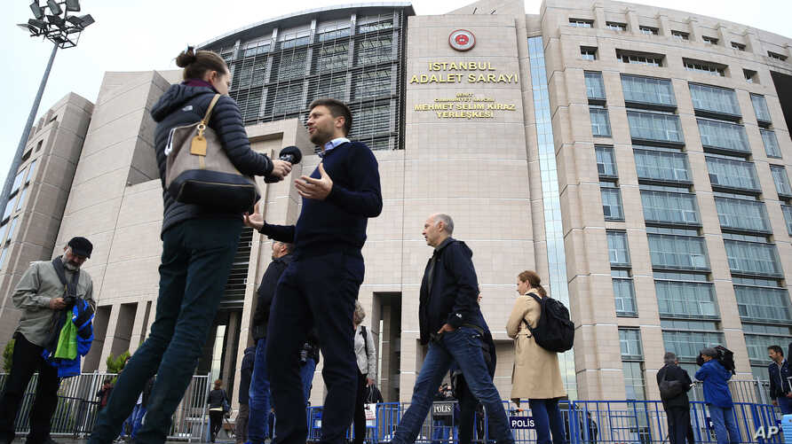 FILE - Human rights activists talk to the media as they stage a protest outside a court in Istanbul, Wednesday, Oct. 25, 2017.