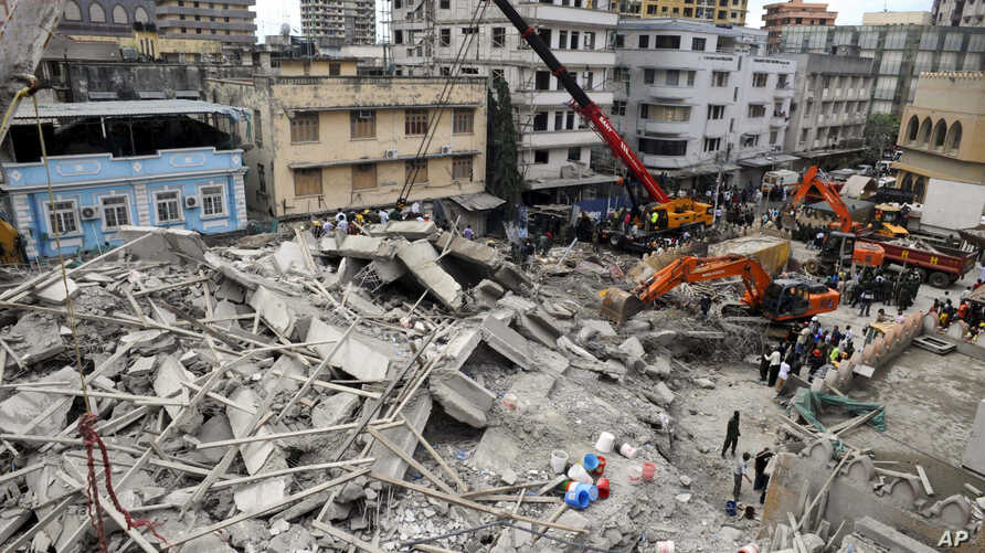 Rescuers using mechanical diggers remove rubble from the site of a collapsed building in downtown Dar es Salaam, Tanzania, Mar. 29, 2013.