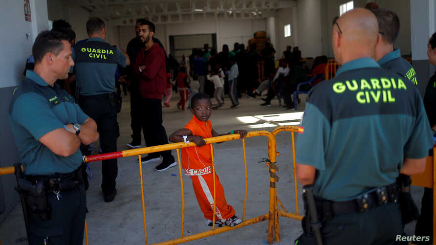 Spanish Civil Guards guard the entrance of a makeshift emergency building where migrants, intercepted aboard dinghies off the coast in the Strait of Gibraltar, rest after arriving on a rescue boat at the port of Barbate, southern Spain, July 28, 2018
