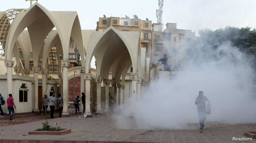 Coptic Christians run inside the main cathedral in Cairo as police fire tear gas during clashes with Muslims standing outside the cathedral April 7, 2013.
