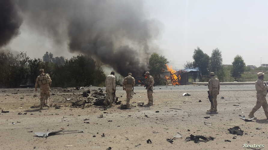 Iraqi security forces inspect the site of a car bomb attack on the outskirts of Diyala province, May 24, 2015.