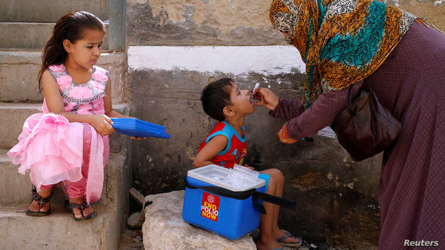 A boy receives polio vaccine drops during an anti-polio campaign, in a low-income neighbourhood in Karachi, Pakistan, April 9, 2018.