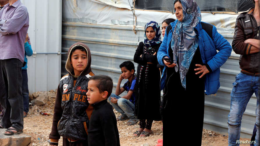 FILE - Syrian refugees woman are seen gathered for a news conference by visiting U.N. High Commissioner for Refugees Filippo Grandi (not pictured), at the Al Zaatari refugee camp, in the Jordanian city of Mafraq, near the border with Syria, Feb. 12,