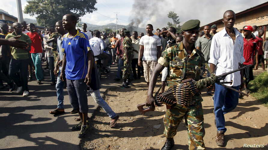 A soldier walks away from protesters in Burundi's capital, Bujumbura, as they clash with riot police.  Monday was the second day of demonstrations against the president's decision to run for a third term, a move critics say violates the constitution.