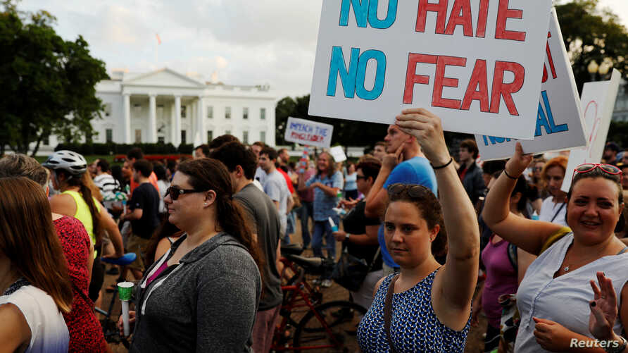 """People gather for a vigil in response to the death of a counter-demonstrator at the """"Unite the Right"""" rally in Charlottesville, outside the White House in Washington, Aug. 13, 2017."""