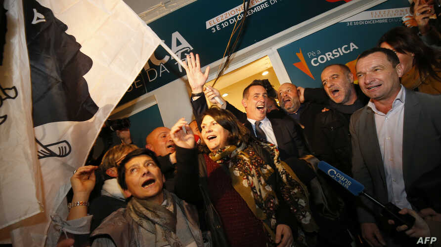 Candidate for the Pe a Corsica nationalist party Gilles Simeoni (C) celebrates with supporters in Bastia, on the French Mediterranean Island of Corsica, Dec. 3, 2017, after the results of the first round of the election were announced.