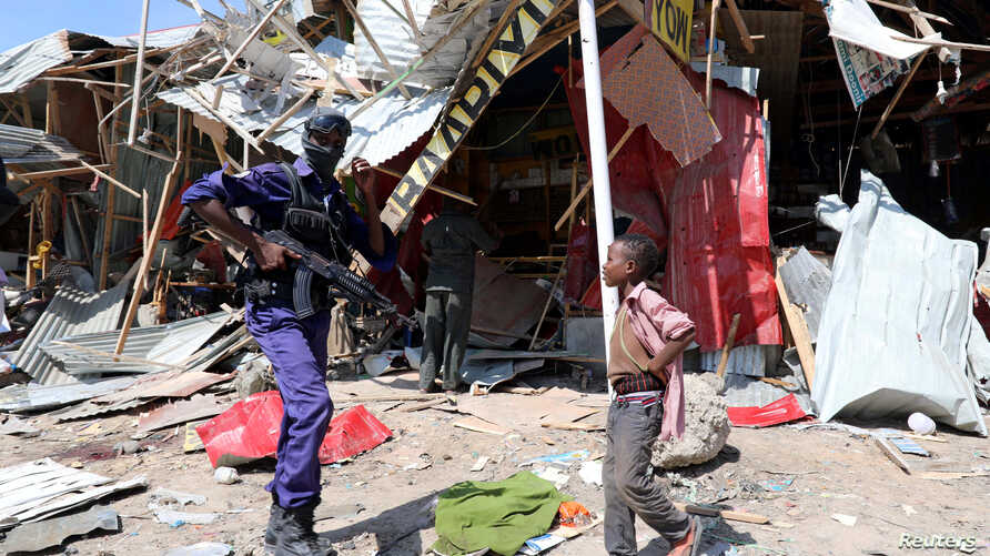 A Somali security officer walks past a child as he secures the scene of an explosion at a market in Wadajir district in Mogadishu, Somalia, Nov. 26, 2018.