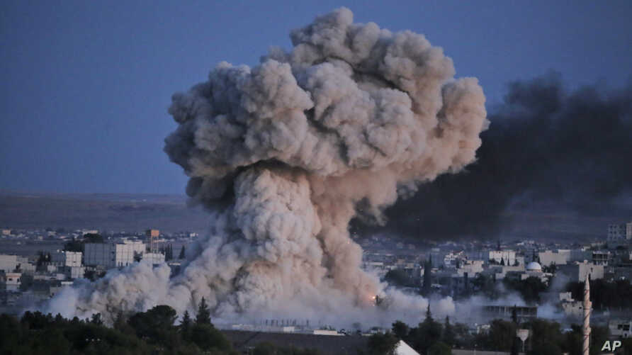 Thick smoke from an airstrike by the U.S.-led coalition rises in Kobani, Syria, as seen from a hilltop on the outskirts of Suruc, at the Turkey-Syria border, Oct. 20, 2014.