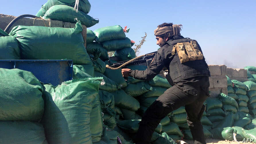 FILE - A member of the tribal groups fighting along with the Iraqi government security forces takes a position behind sandbags during clashes with jihadists in the Hosh district of Ramadi as the Islamic State jihadist group launched a coordinated att