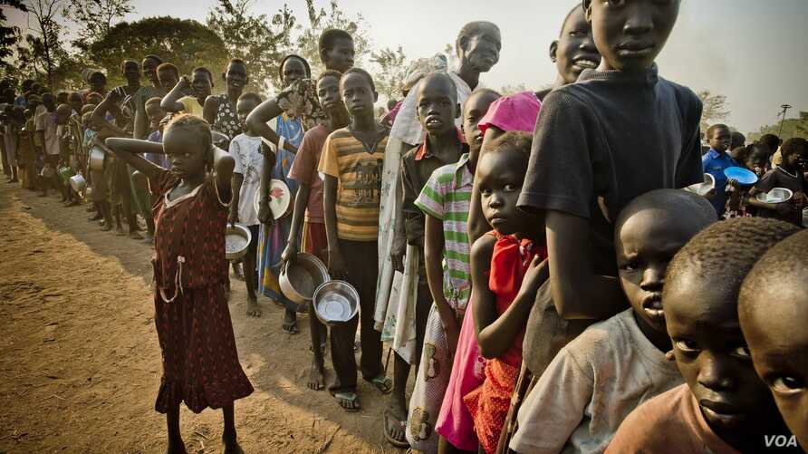 South Sudanese refugees wait in line to get food at Dzaipi transit camp in northern Uganda.