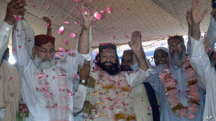 In this photo taken on July 15, 2011, Malik Ishaq, center, a leader of the banned Sunni Muslim group Lashkar-e-Jhangvi, and his colleagues raise hands to response their supporters who greeted him with rose-petals upon his arrival at hometown after hi