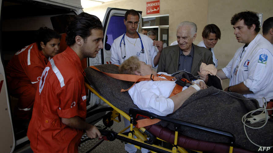 FILE - Lebanese-French Evelyne Ghandour, who suffers from heart problems, talks with her husband Georges, as workers of the International Committee of the Red Cross (ICRC) carry her into an ambulance at a hospital in Beirut.