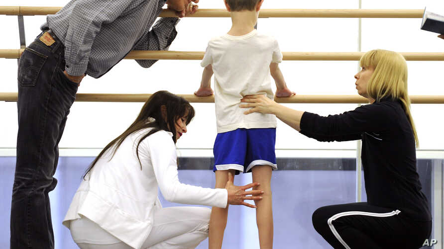 FILE - Artistic director of the School of American Ballet (SAB), Peter Martins (L) and SAB teachers look over an eight-year-old student during the school's 2009 Spring Auditions at Lincoln Center, in New York, May 5, 2009.