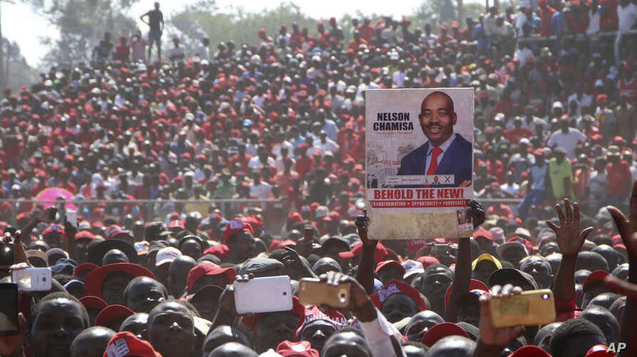 Movement for Democratic Change (MDC) supporters hold a poster of leader Nelson Chamisa during the party's 19th-anniversary celebrations in Harare, Zimbabwe, Saturday, Oct. 27, 2018.