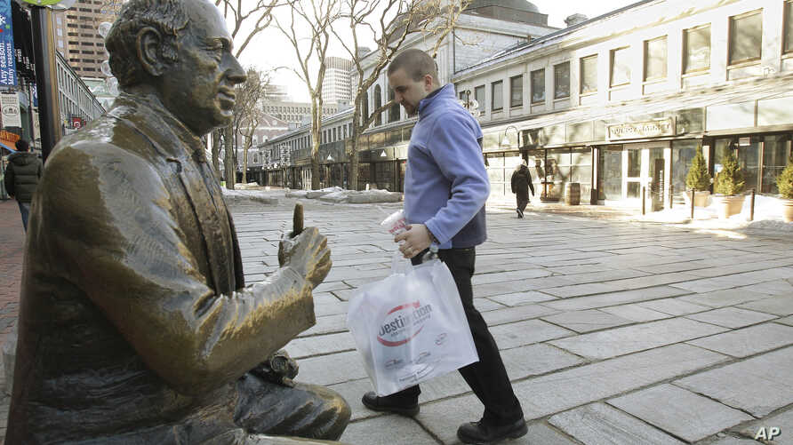 FILE - A shopper walks past a bronze sculpture of famed Boston Celtics coach Red Auerbach at Qunicy Market in downtown Boston.