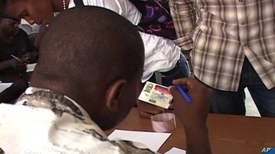 A Haitian worker at the US military's data collection center in Port-au-Prince checks identification from people needing help.