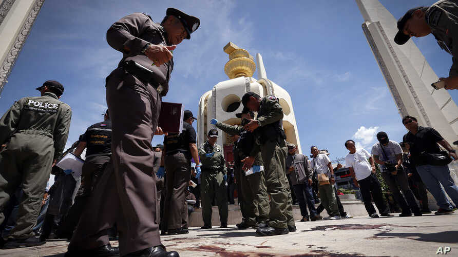 Thai police investigate following an overnight shooting attack at Democracy Monument in Bangkok, Thailand, Thursday, May 15, 2014.