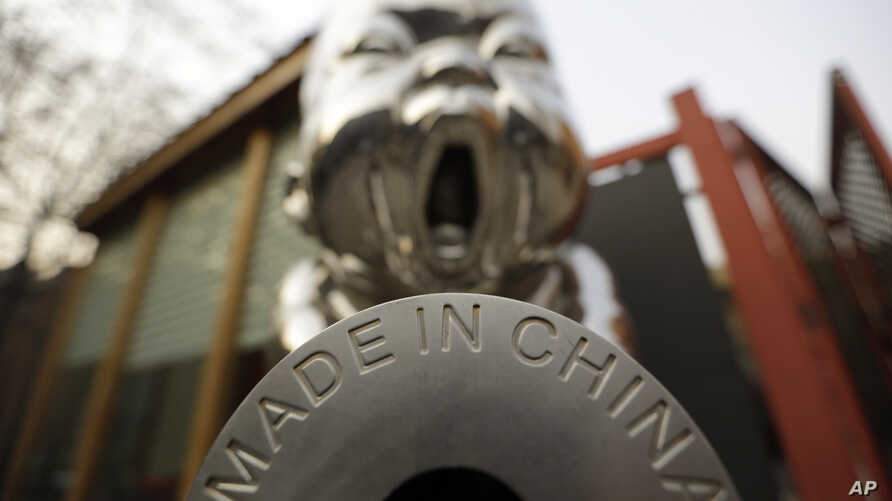 """FILE - A sculpture is displayed with the phrase """"Made in China,"""" at the 798 Art District in Beijing, China, Nov. 21, 2012."""