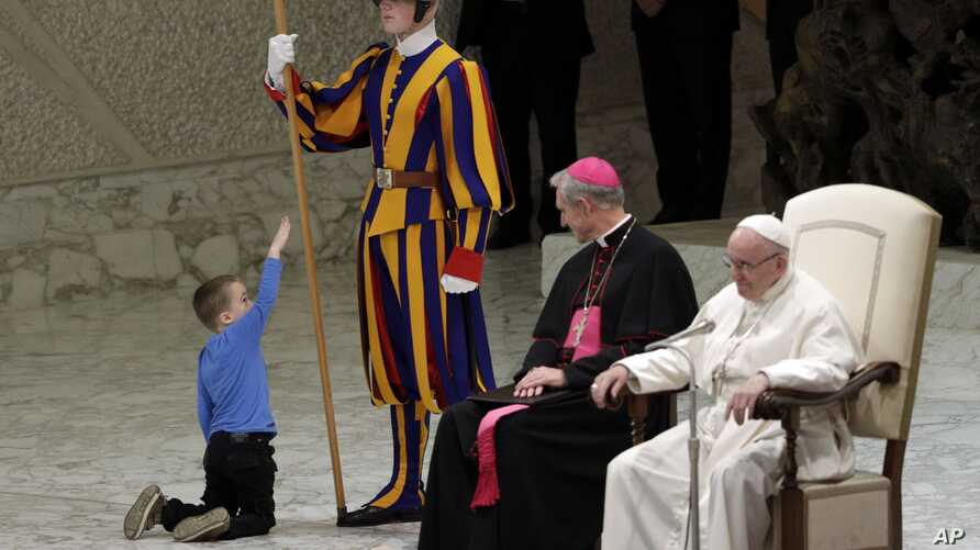 A child plays with a Swiss guard in the Paul VI Hall at the Vatican, Wednesday, Nov. 28, 2018. Pope Francis has praised the freedom, albeit undisciplined, of a hearing-impaired child who climbed onto the stage during his general audience to play.