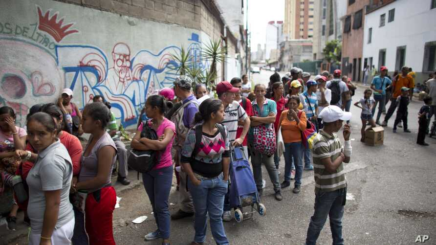 FILE - People wait in line for subsidized food staples, such as beans, rice, tuna and powdered milk, provided by the government program CLAP, which stands for Local Committees of Supply and Production, in Caracas, Venezuela, May 16, 2018.