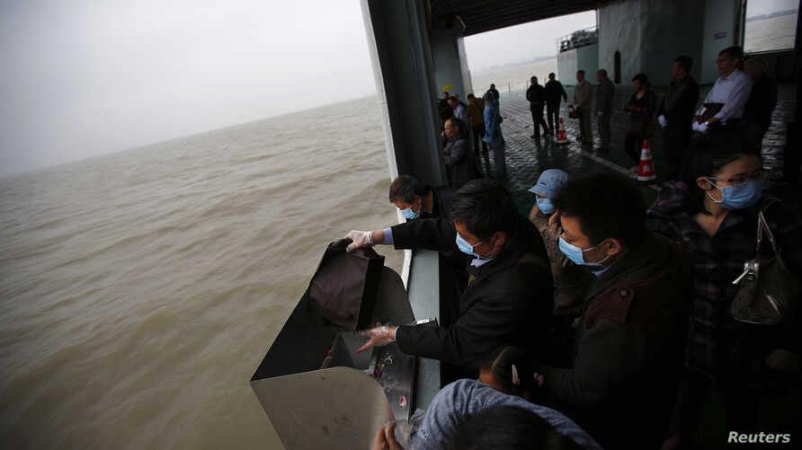 A man scatters the ashes of his parents and grandmother into the ocean during a sea burial ceremony near Shanghai, May 10, 2014.