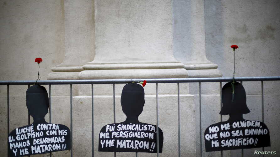"""Cut-out depicting victims of human rights abuse during the rule of former dictator Augusto Pinochet hang on a fence next to the """"La Moneda"""" Presidential Palace during a rally in Santiago, Sept. 11, 2015."""