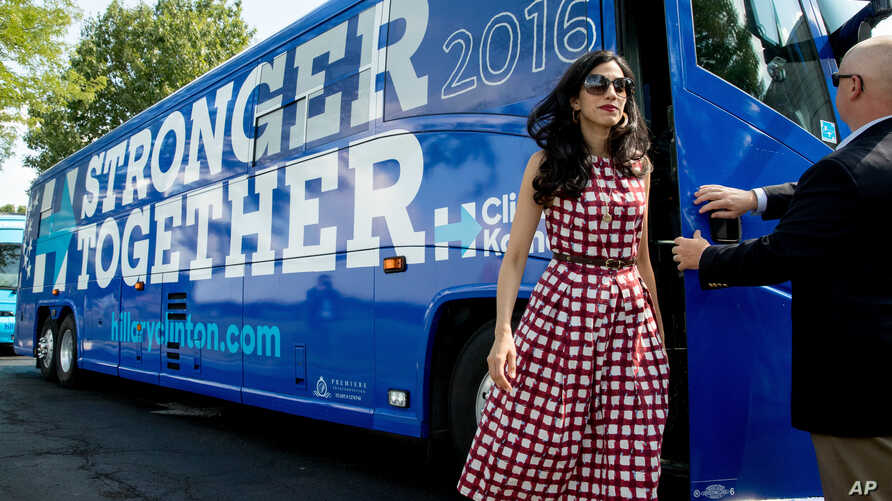 Huma Abedin, center, an aide to Democratic presidential candidate Hillary Clinton, gets of a campaign bus for Democratic presidential candidate Hillary Clinton and Democratic Vice Presidential candidate, Sen. Tim Kaine, D-Va.