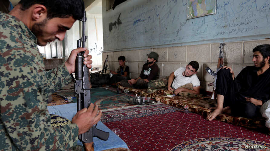A rebel fighter from Jaysh al-Sunna, operating under a coalition of rebel groups called Jaish al-Fatah, or the army of conquest, prepares his weapon as others rest in Aziziyah village, southern Aleppo countryside, Syria, May 17, 2016.