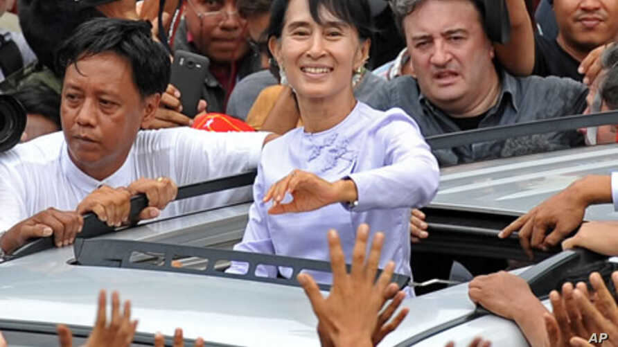 Burma's opposition leader Aung San Suu Kyi (C) waves to the crowd as she leaves National League for Democracy (NLD) headquarters after addressing journalists and supporters in Rangoon on April 2, 2012.