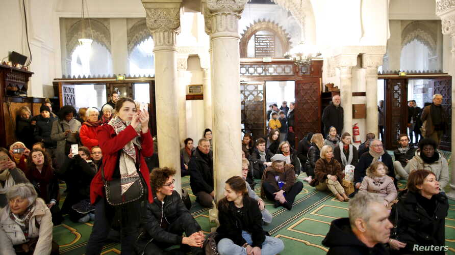 Visitors watch members of the Muslim community praying in the Paris Grand Mosque during an open day weekend for mosques in France, Jan. 10, 2016.