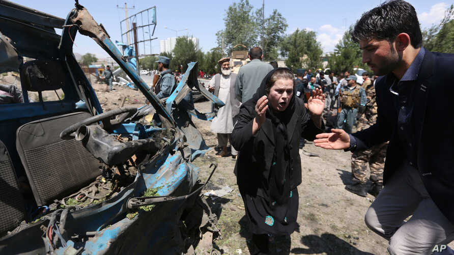 FILE - An Afghan woman cries out at the site of a suicide attack on a NATO convoy in Kabul, Afghanistan, June 30, 2015.