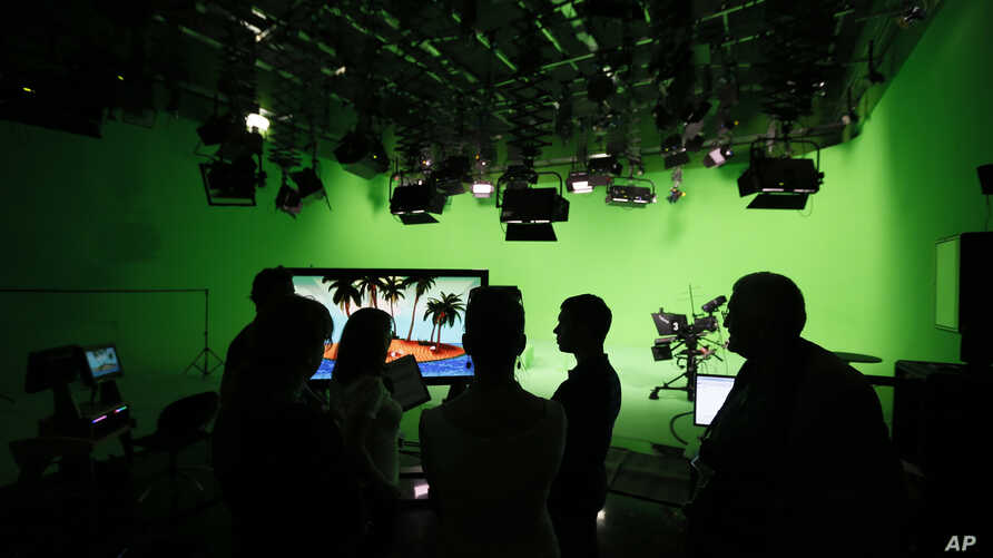 """FILE - employees of the """"Russia Today"""" television channel prepare for a visit by Russian President Vladimir Putin to Russia Today's new headquarters in Moscow, Russia."""
