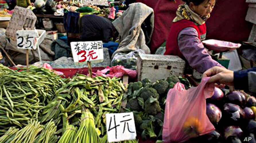 A customer picks up a plastic bag of peppers at a fruit and vegetable market in Beijing (file photo - 17 Nov 2010)
