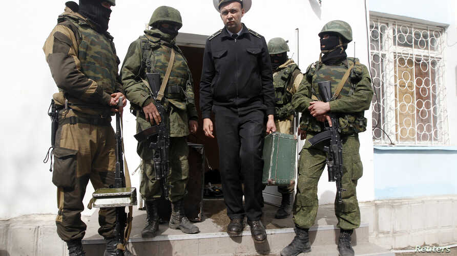 FILE - A Ukrainian naval officer (C) passes by armed men, believed to be Russian servicemen, as he leaves the naval headquarters in Sevastopol, March 19, 2014.
