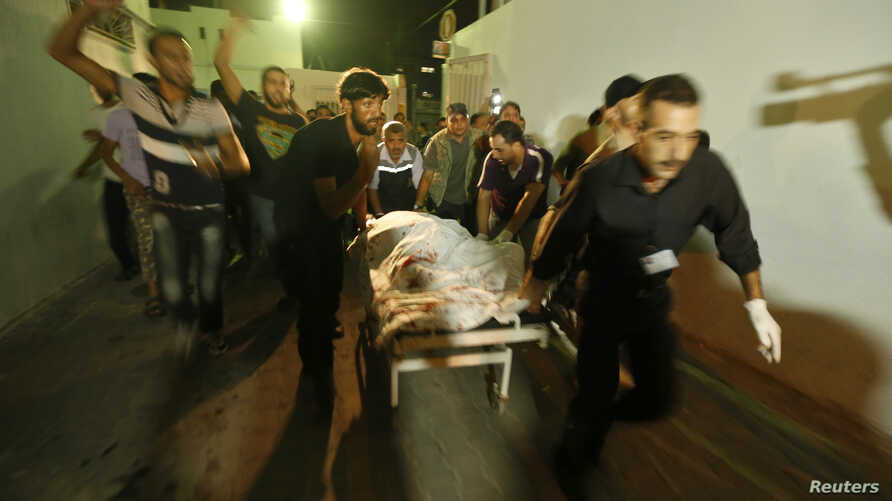 Palestinians wheel the body of a militant at a hospital, following an Israeli air strike in the northern Gaza Strip October 13, 2012.