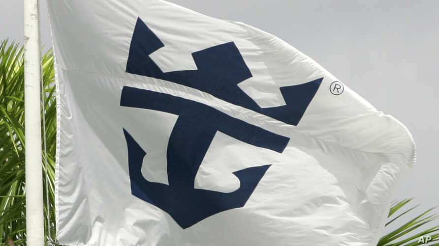FILE - The Royal Caribbean Cruises Ltd., flag waves outside the headquarter building in Miami, Florida.