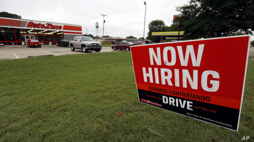 FILE-  A bilingual help wanted sign for Auto Zone, a retailer of aftermarket automotive parts and accessories, is posted outside the store in Canton, Miss., Sept. 27, 2018.