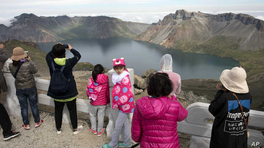 In this Saturday, Aug. 18, 2018, photo, Chinese tourists take in the sight from a viewing platform overlooking the caldera of Mount Paektu near Samjiyon in North Korea.