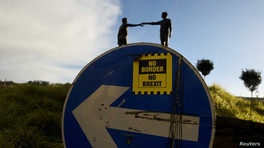"FILE - A ""No Border, No Brexit"" sticker is seen on a road sign in front of the Peace statue entitled ""Hands Across the Divide"" in Londonderry, Northern Ireland, Jan. 22, 2019."