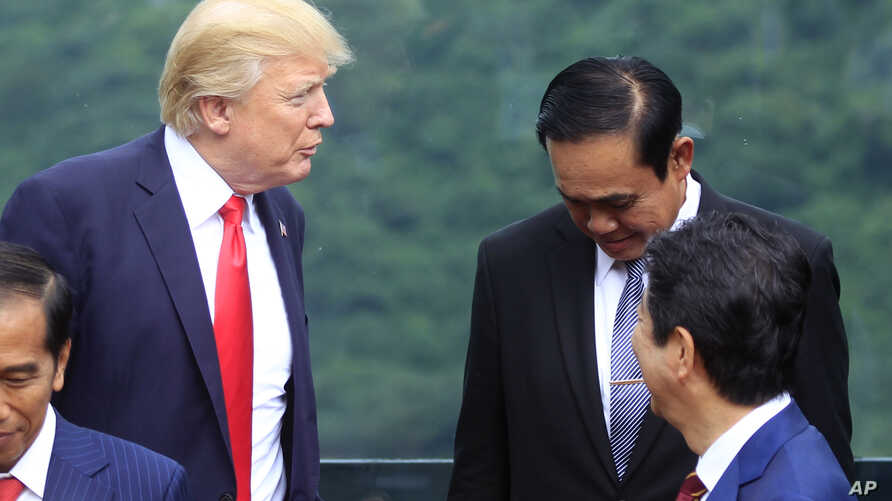 FILE - U.S. President Donald Trump, left, talks with Thai Prime Minister Prayuth Chan-ocha during the family photo session during the Asia-Pacific Economic Cooperation (APEC) Summit in Danang, Vietnam, Nov. 11, 2017.